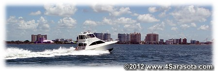 Powerboat cruises past downtown Sarasota, FL with the Van Wezel in the background.